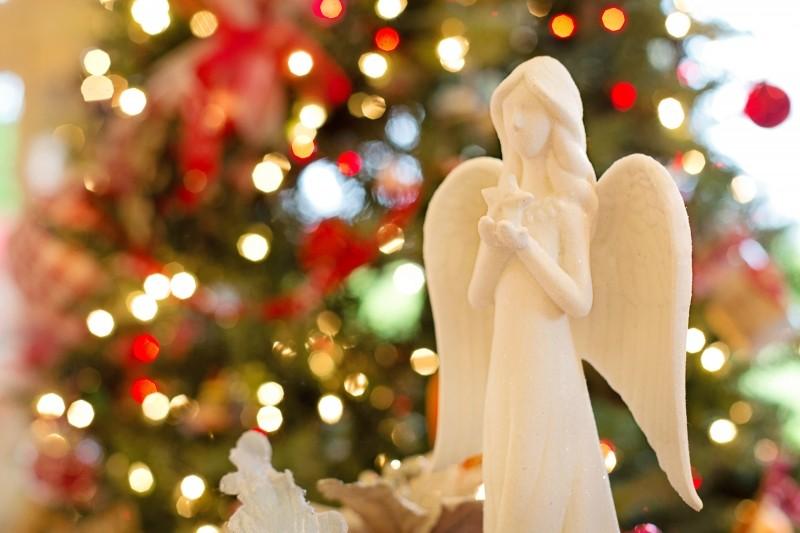 figurine_of_angel_holding_star_against_illuminated_christmas_tree